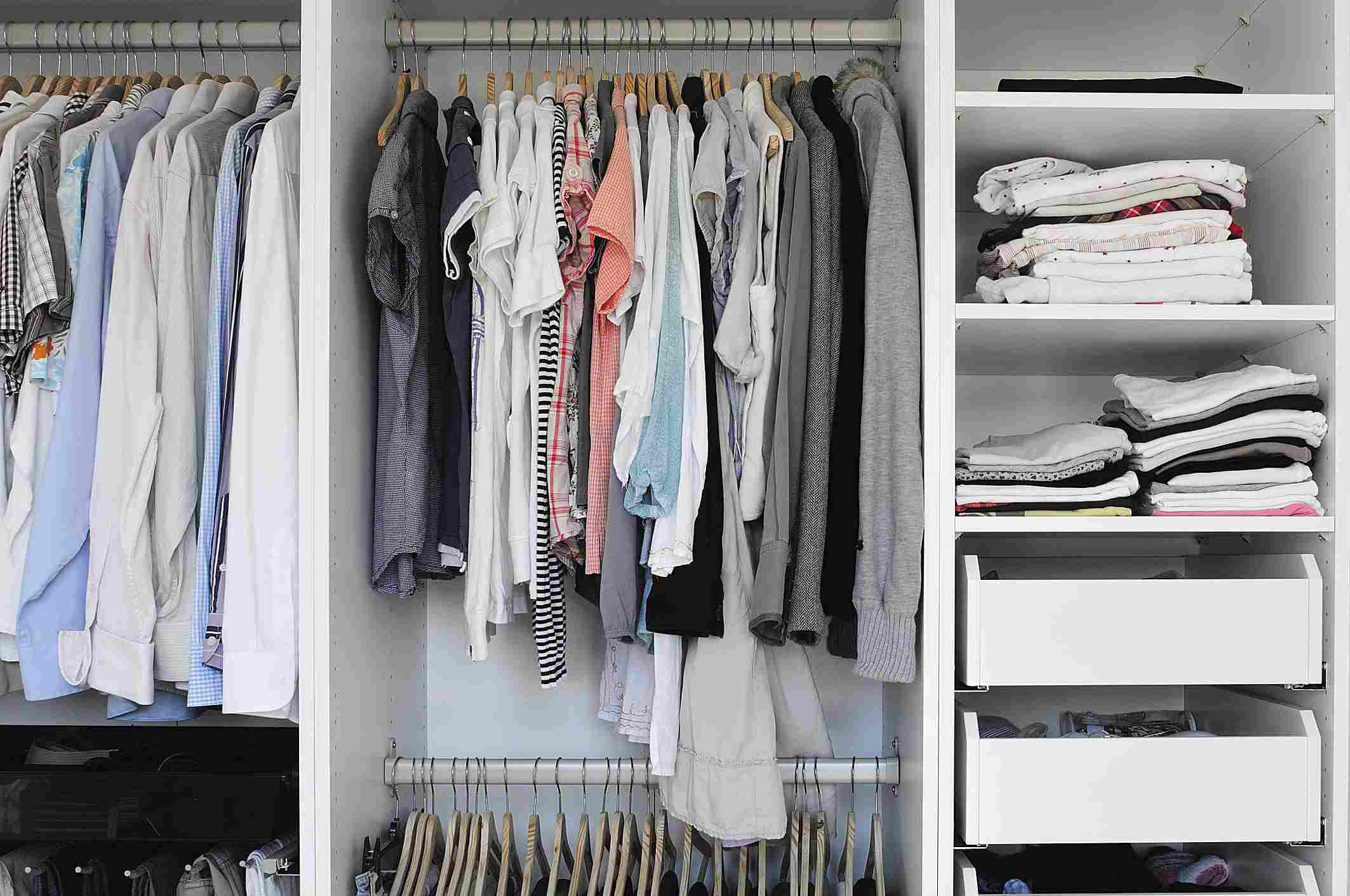 An organized closet with shirts hanging and pants folded.