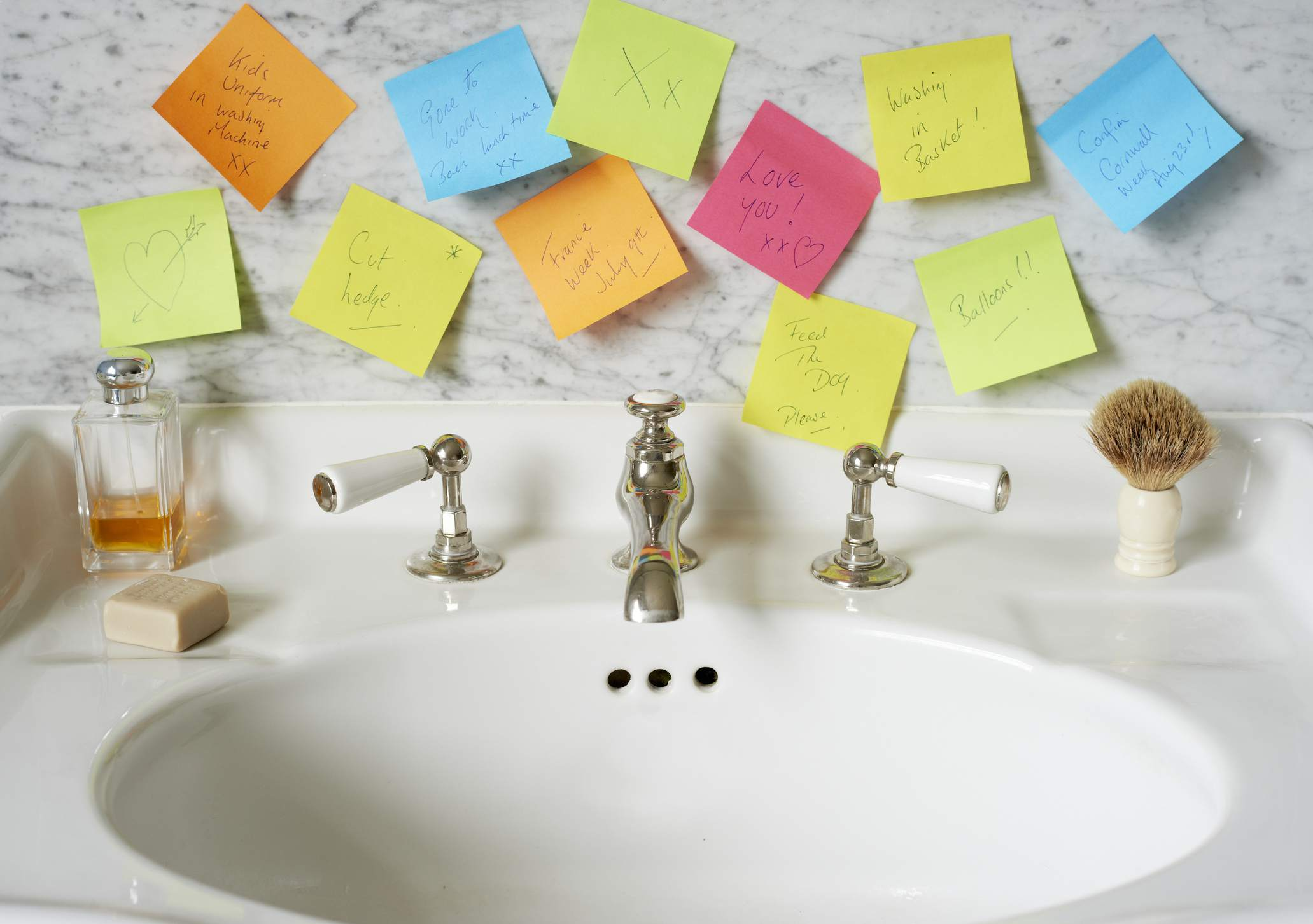Sticky note reminders above a bathroom sink