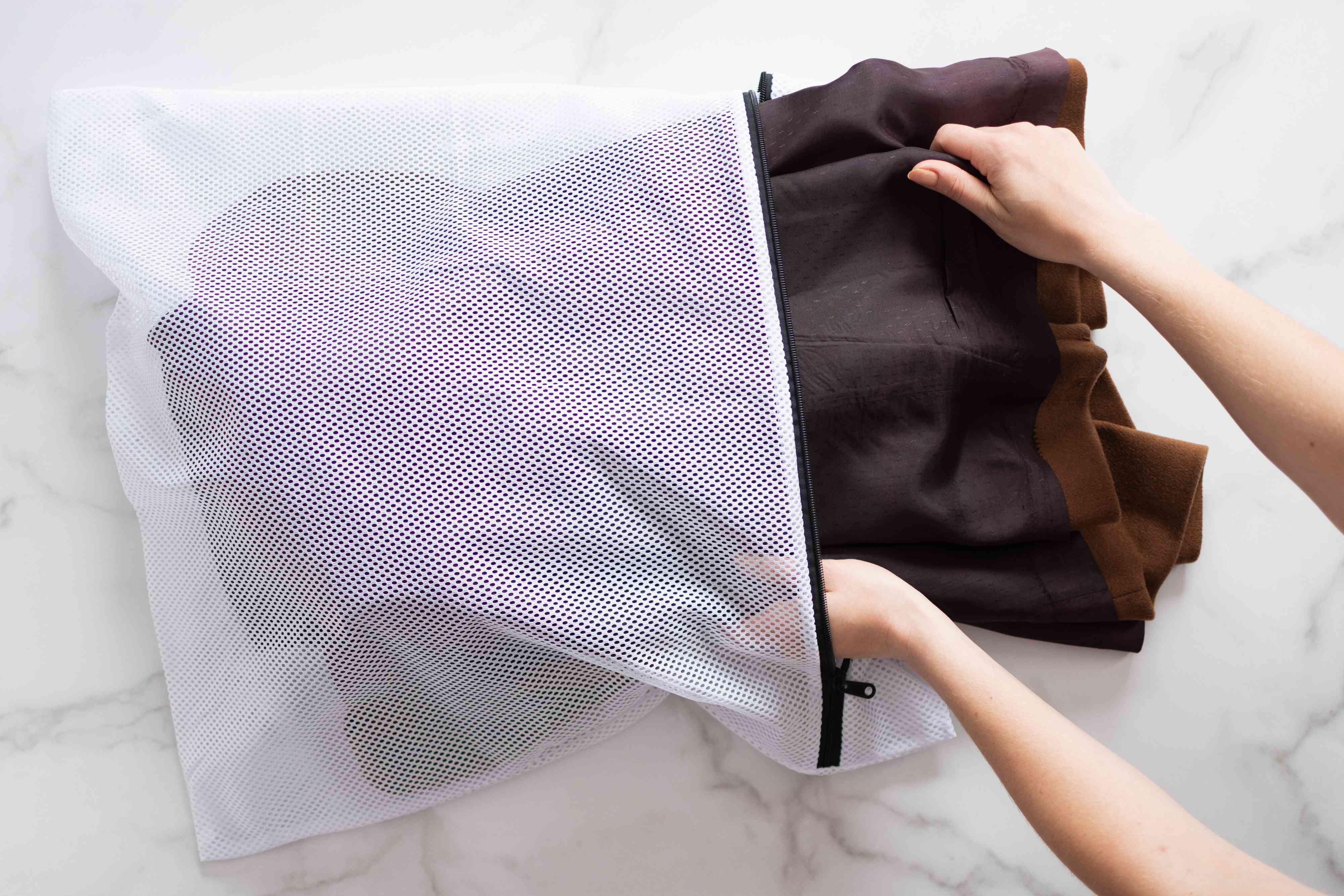 Brown wool coat placed into large mesh bag to be added to washing machine