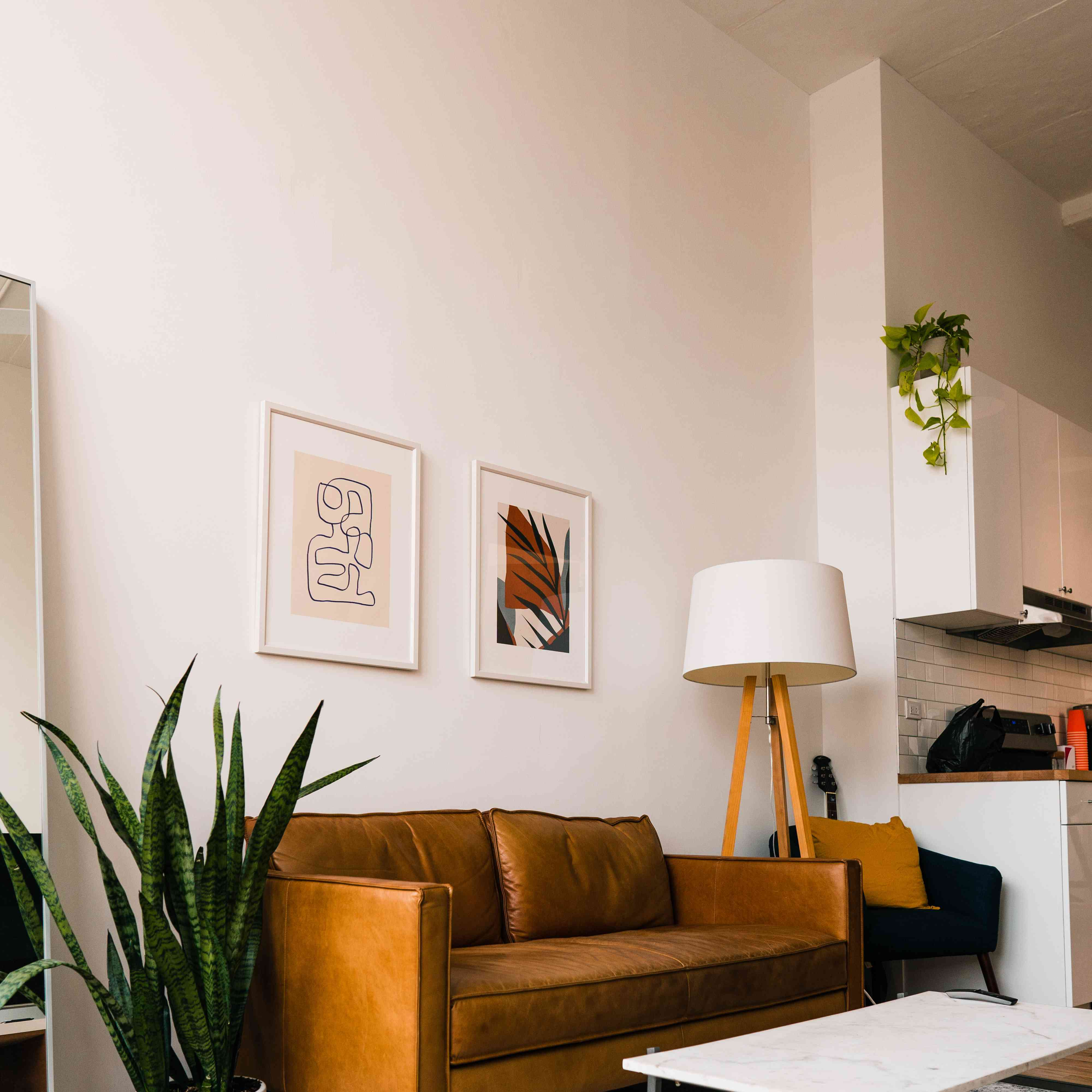 Living room with leather sofa, plant, and artwork