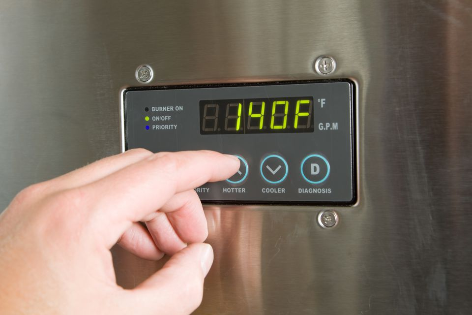 A hand turning up a tankless water heater temperature