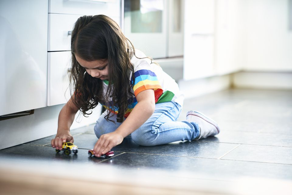 girl playing with toy cars in kitchen