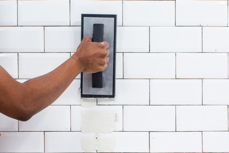 Grout applied to white ceramic wall tiles with rubber float