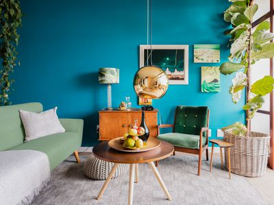 Living room with teal colored walls, light green seating and wooden furniture covered with houseplants