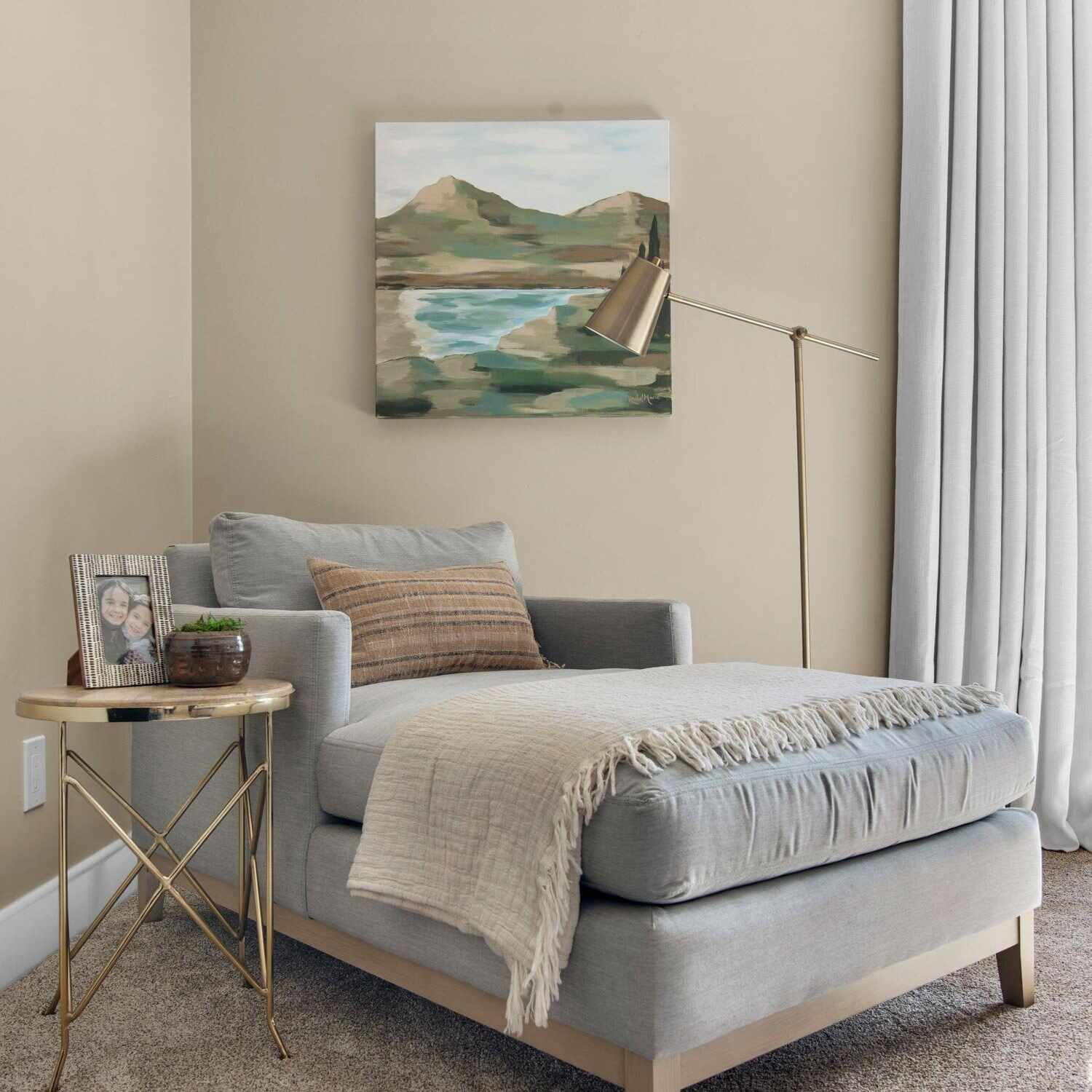gray chaise lounger with golden metal accent table beside it, painting hanging above
