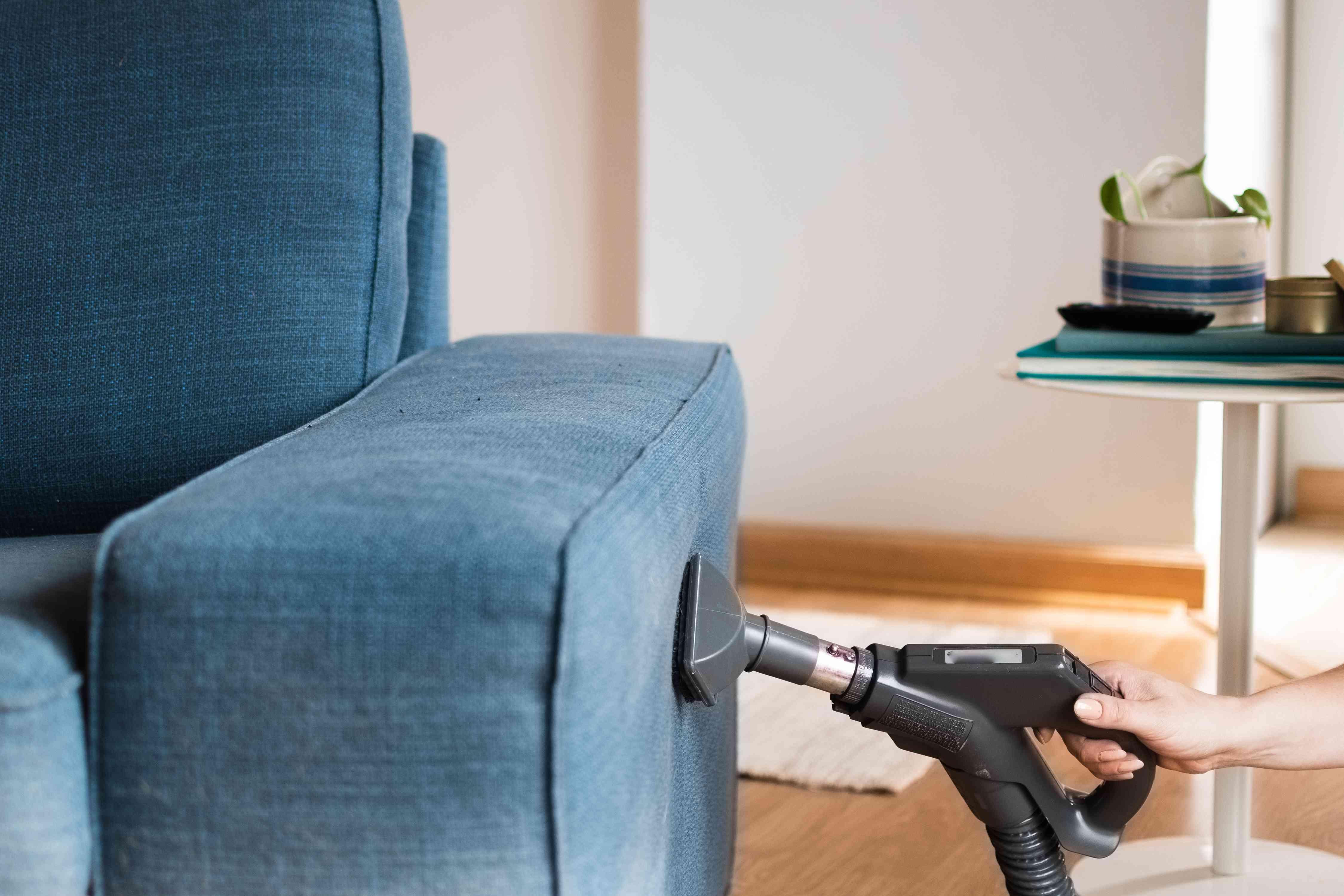 Chân không HEPA đi qua mặt của chiếc ghế dài bọc nệm màu xanh đậm