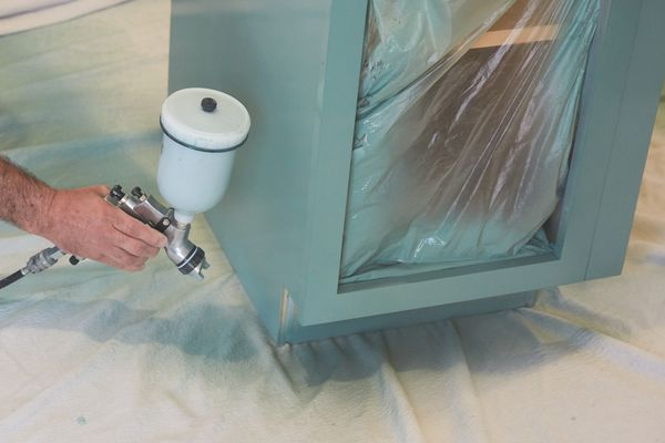 Kitchen cabinets being spray painted mint green with HVLP paint sprayer