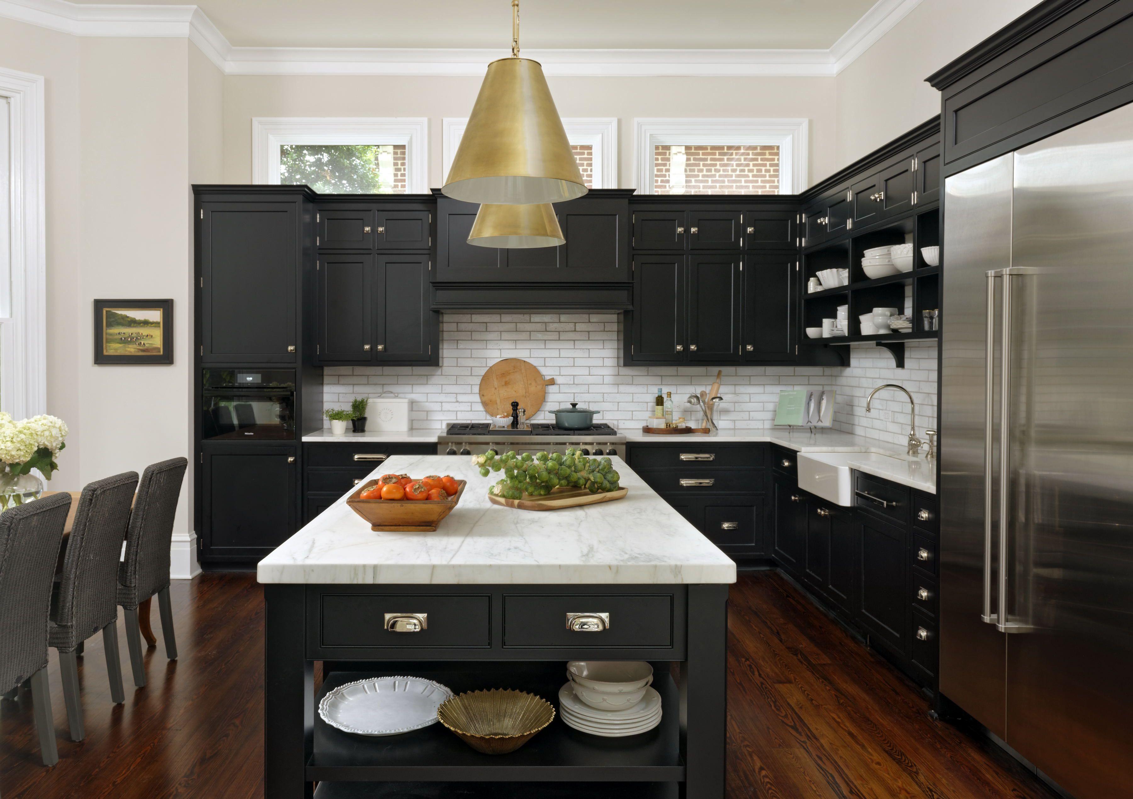 Cocina clásica negra con azulejos blancos, isla de encimera de mármol blanco y electrodomésticos de acero inoxidable y herrajes plateados y dorados