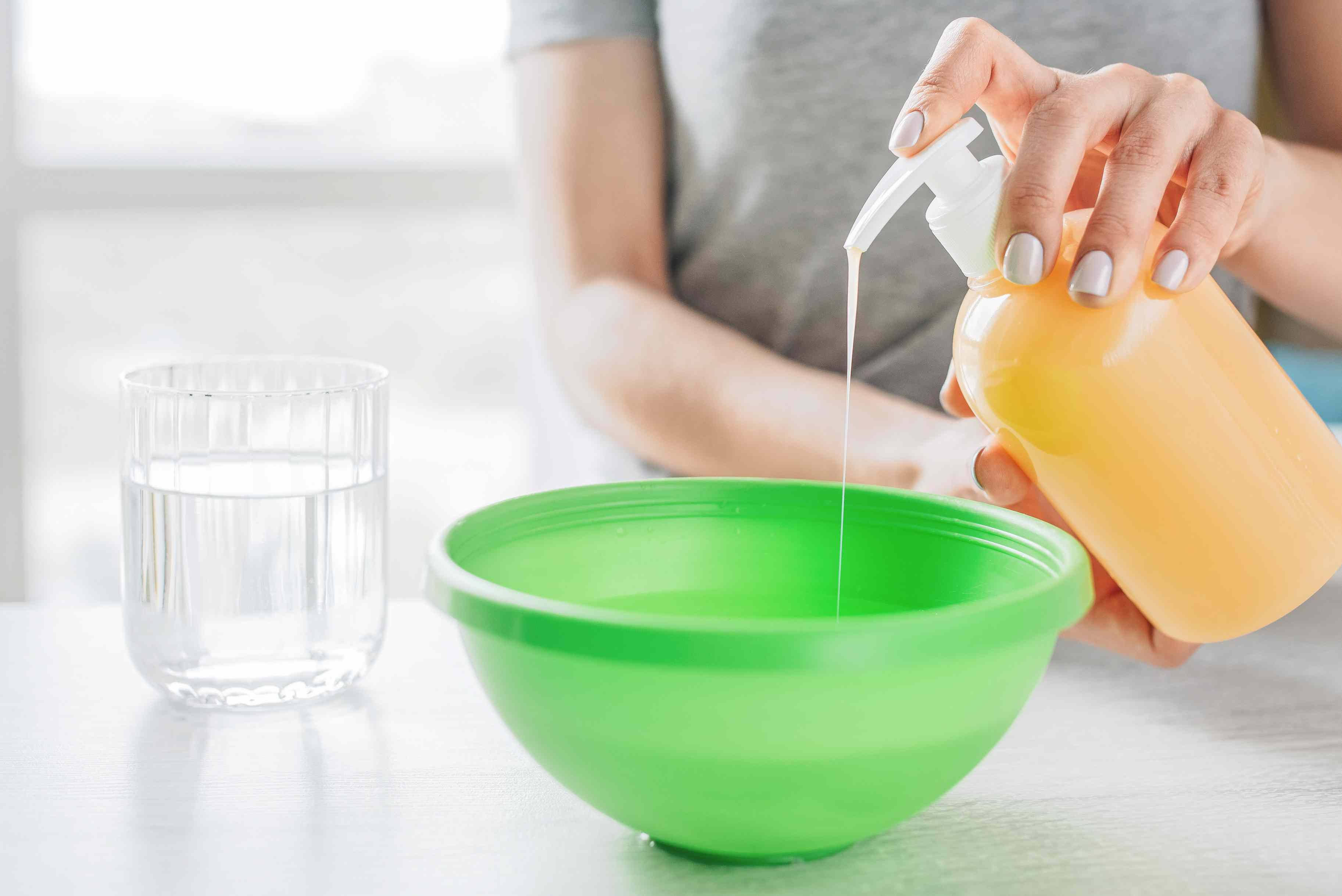 Liquid hand soap pumped into green bowl next to cup of water