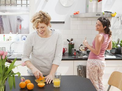 Female friends making breakfast in kitchen