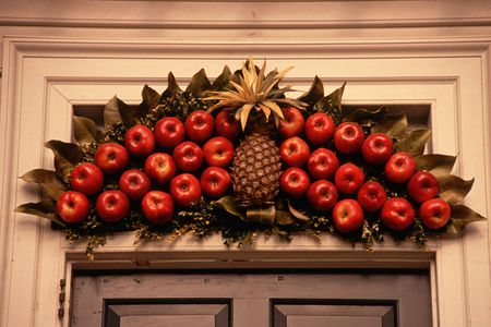 Fruit (apples and a pineapple) displayed over a doorway as an outdoor Christmas decoration