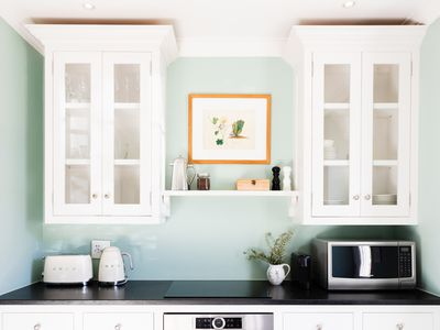 DIY kitchen white cabinets with decorated black countertop and mint-colored wall