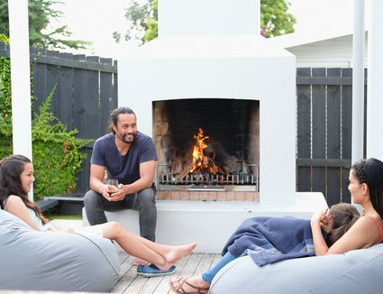 Family is relaxing at home in the afternoon on the outdoor terrace in the backyard - stock photo