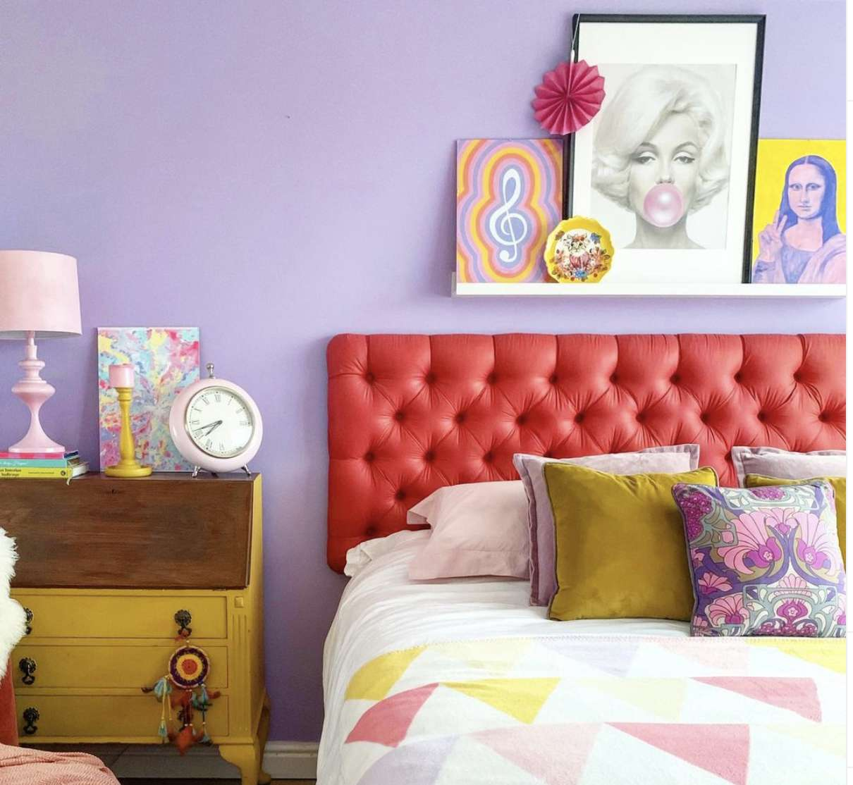 brightly colored eclectic bedroom with purple walls, triangle pattern comforter, vintage style yellow dresser