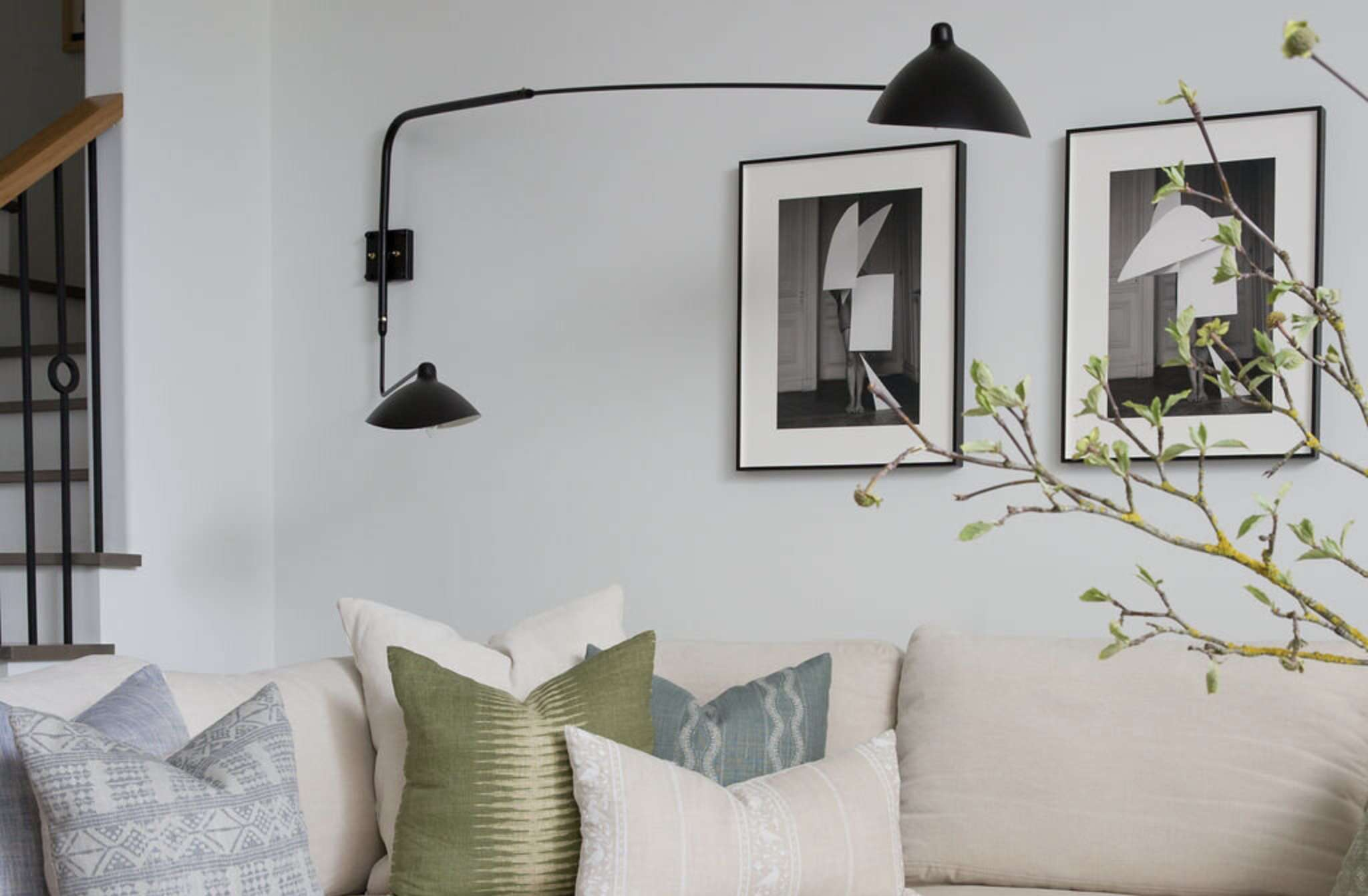 living room with black, gray, and white artwork, black sconces hanging in corner behind couch