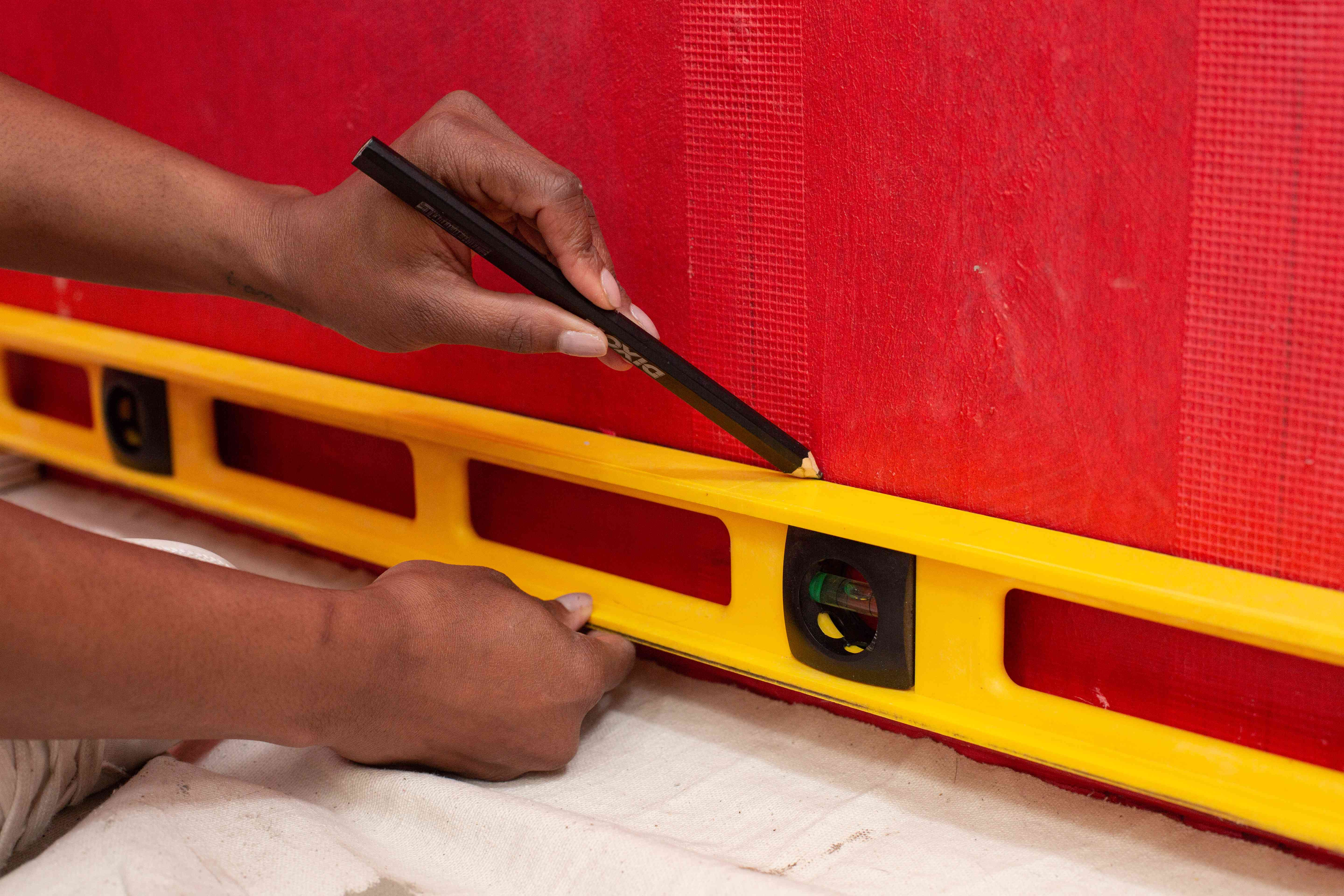 Yellow bubble level under pencil making line on red wall