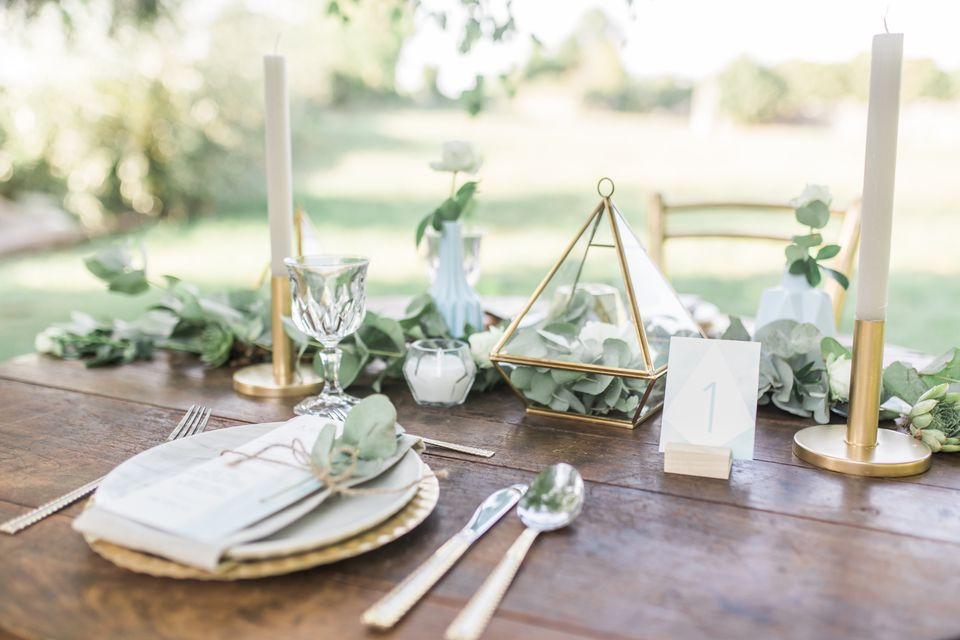 Table setting for an event party or wedding reception, decorated with geometric shape vases, gold candles eucalyptus branches and flowers.