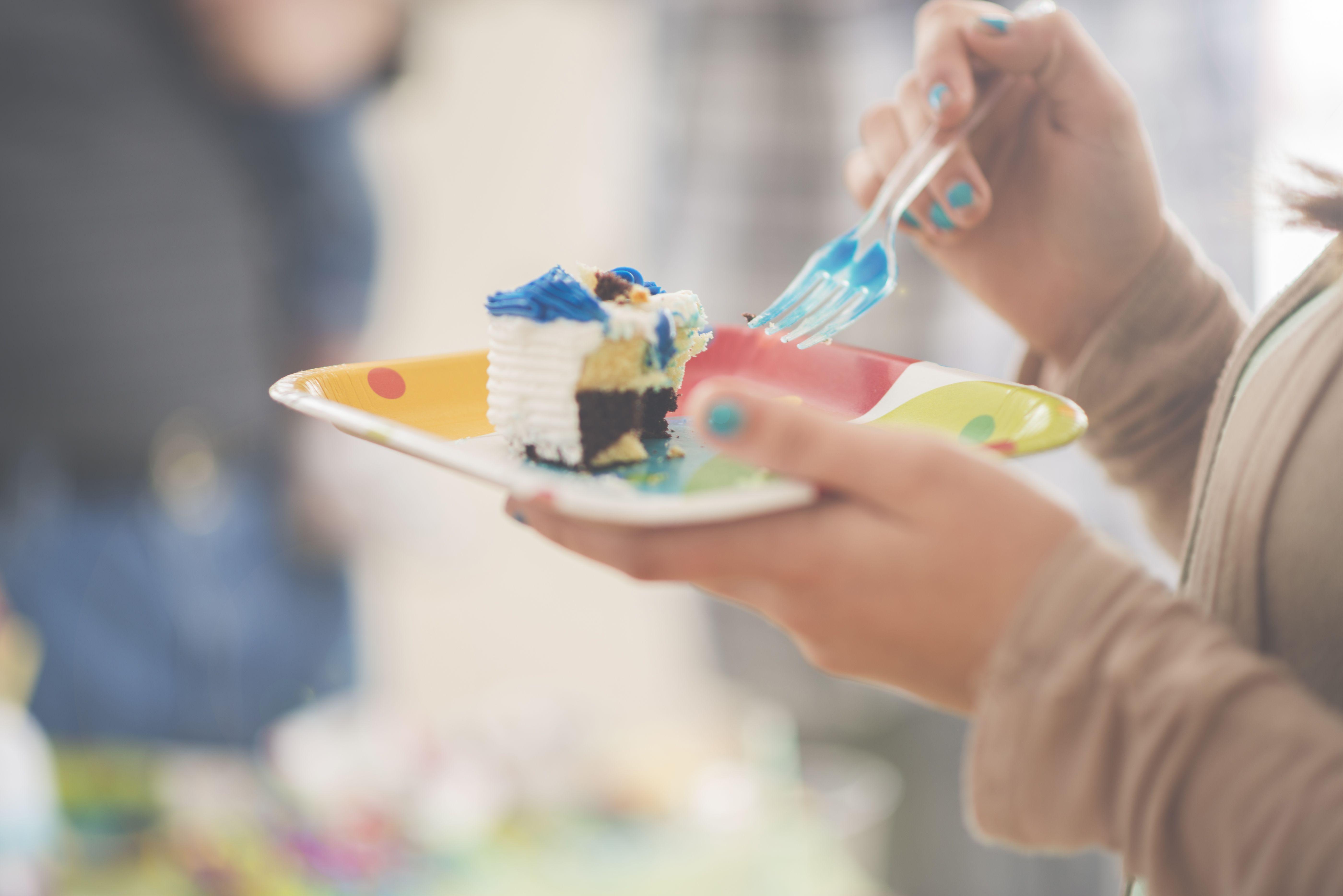 Girl eating slice of birthday cake