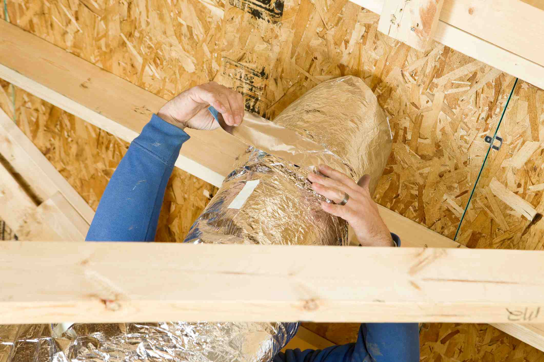 Worker Insulating an attic vent duct with aluminum foil