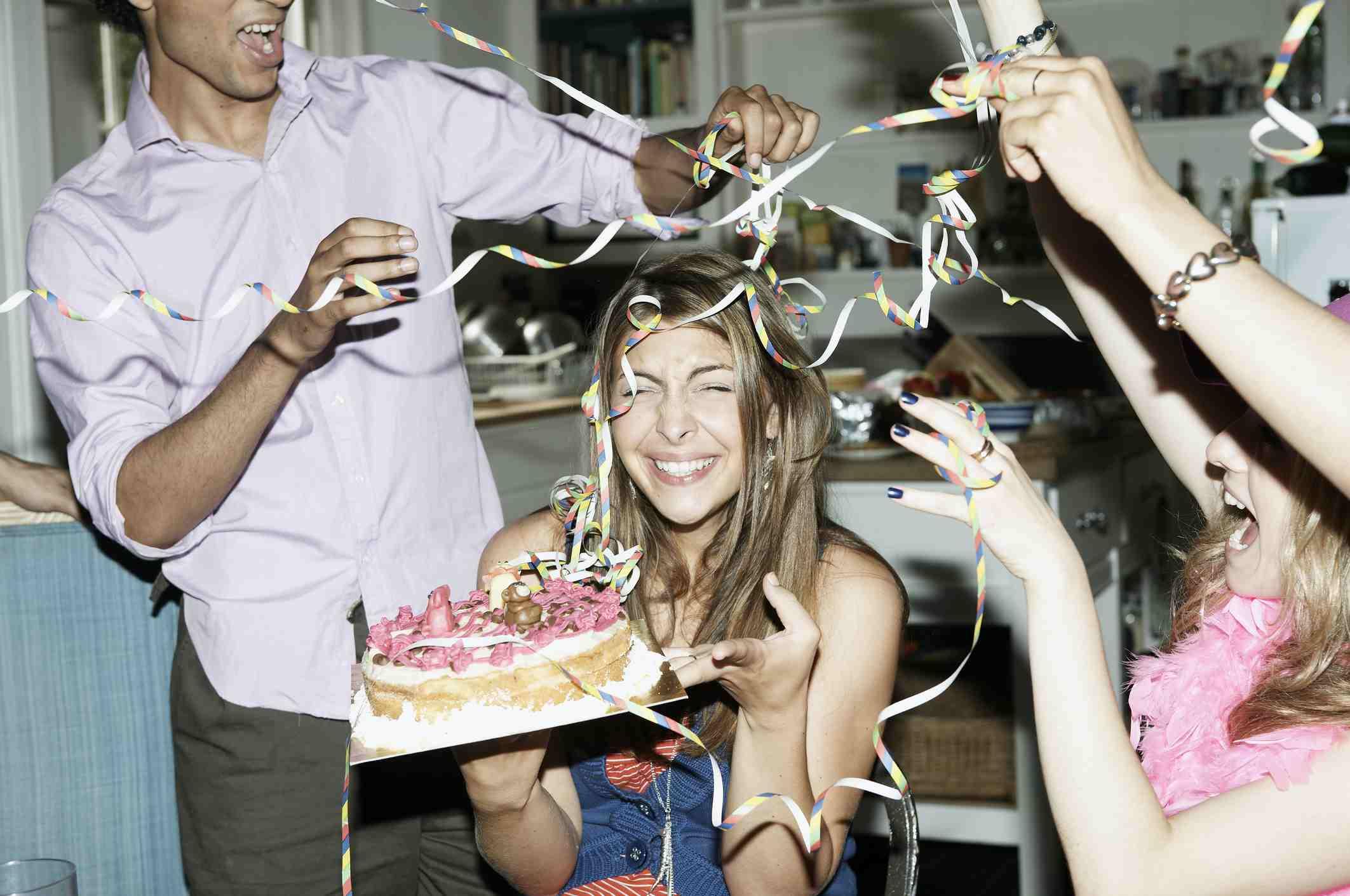 Friends releasing birthday streamers on birthday girl