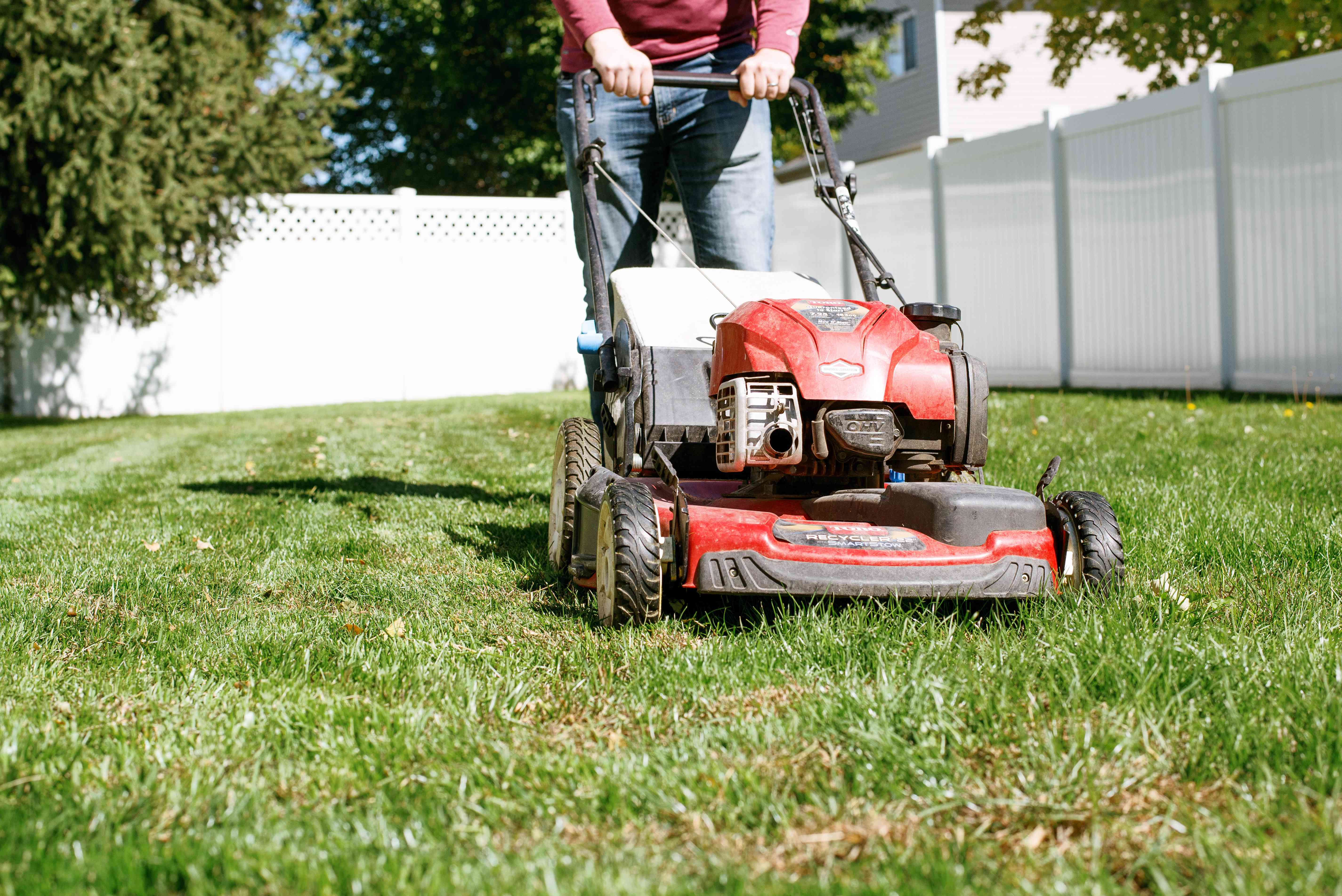 Yard being mowed with lawn mower to repel ticks naturally