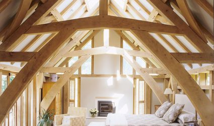 A light and airy bedroom in an attic with natural wood beams, plants, and a fireplace.