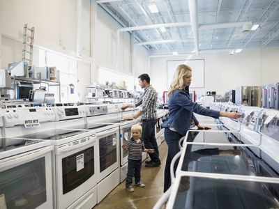 Young family shopping for stoves in an appliance store