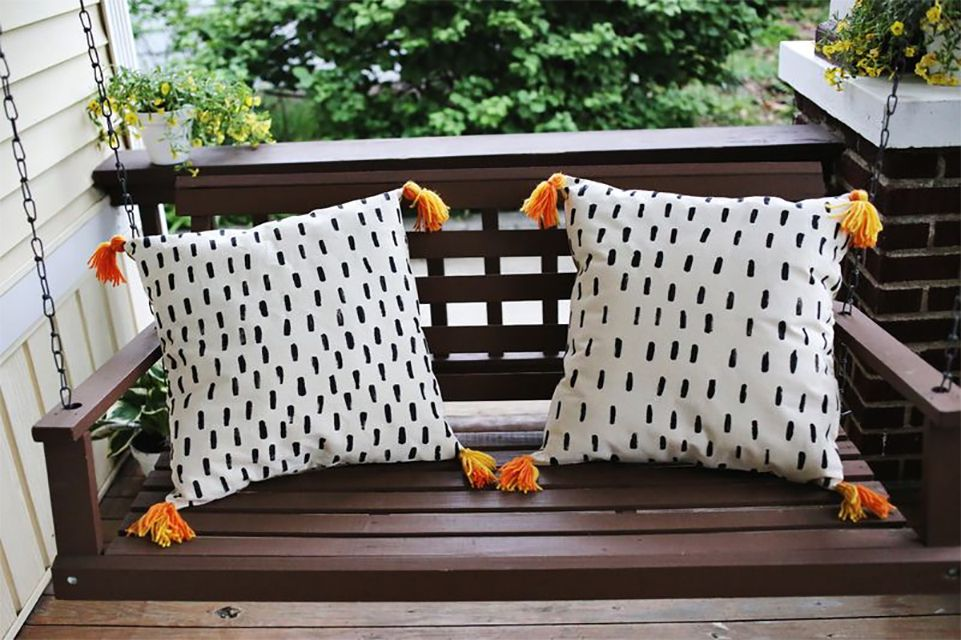 Two throw pillows on a porch swing