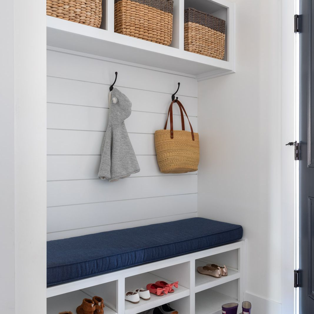 an entryway/mudroom with built in storage with bins, hooks, and shelving by Melanie Love