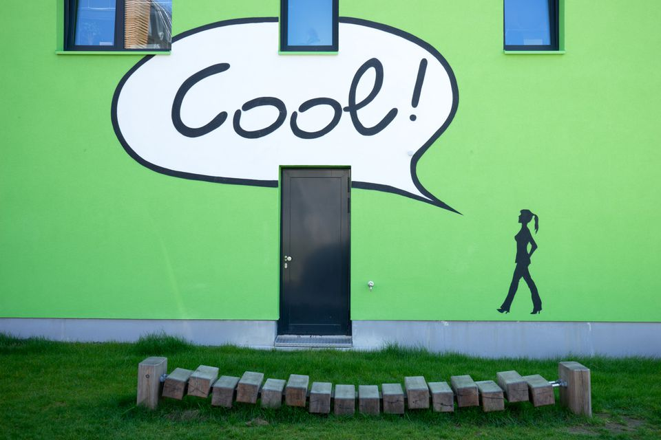 "Green apartment building with painted figure with voice balloon that says ""Cool!"""