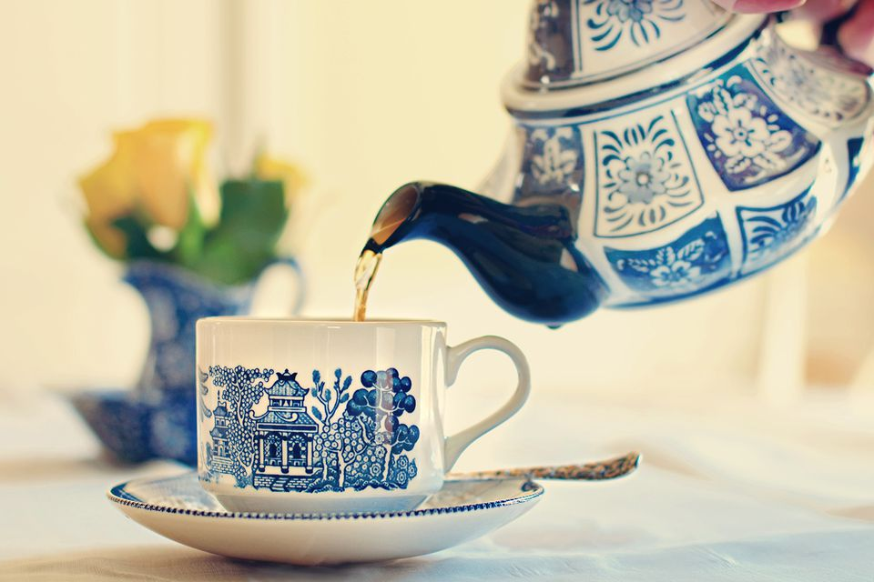 Blue and white china teapot pouring tea into china tea cup