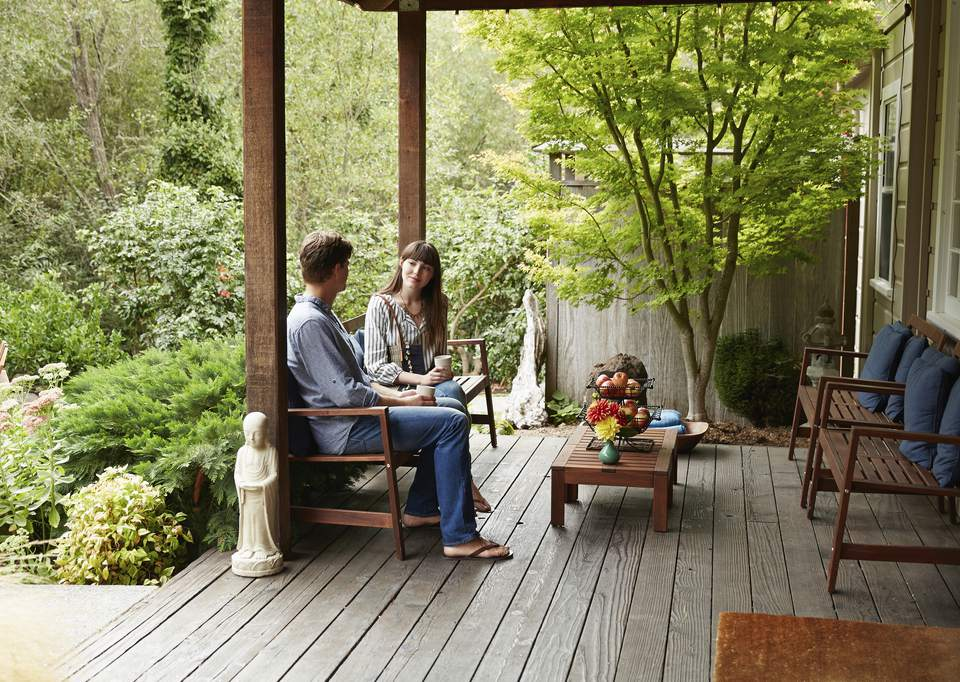 Caucasian couple talking on wooden patio