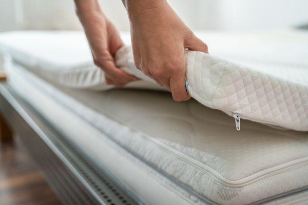 Woman adjusting mattress topper on mattress