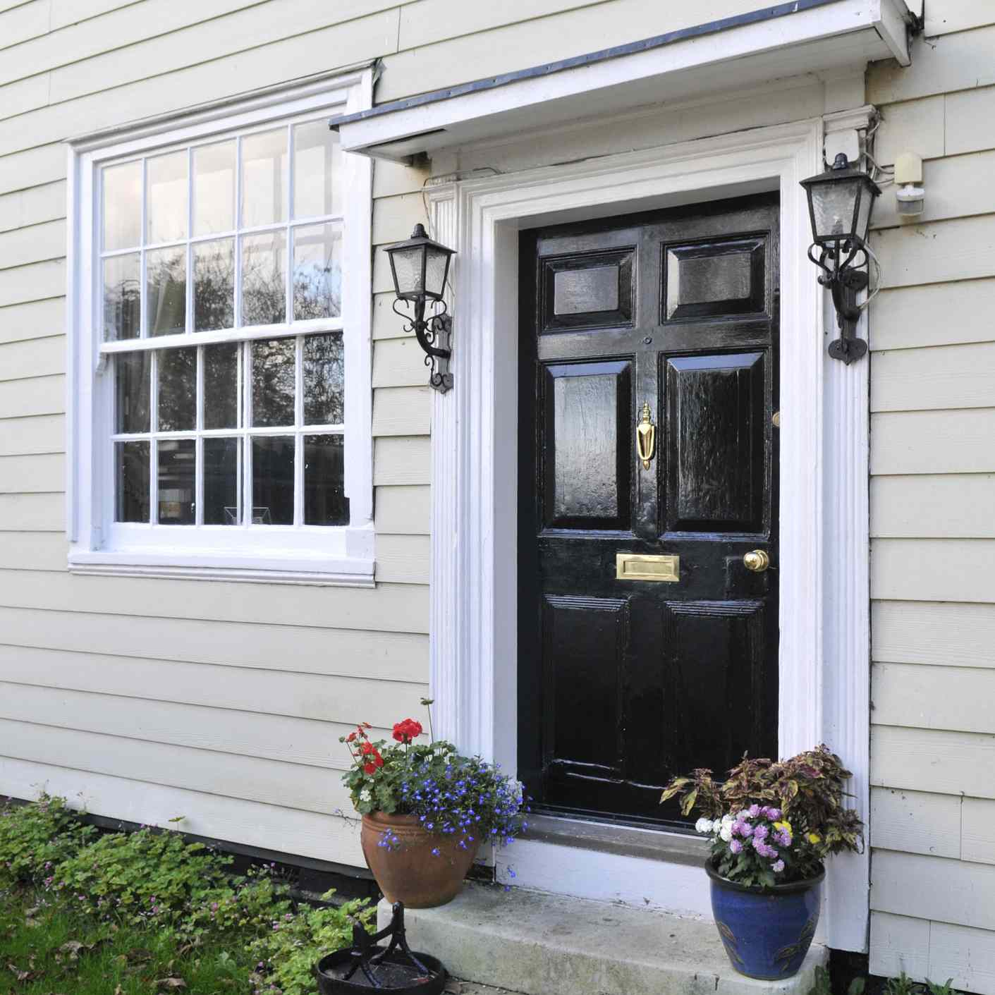 A black front door on a white house with steps and flowers