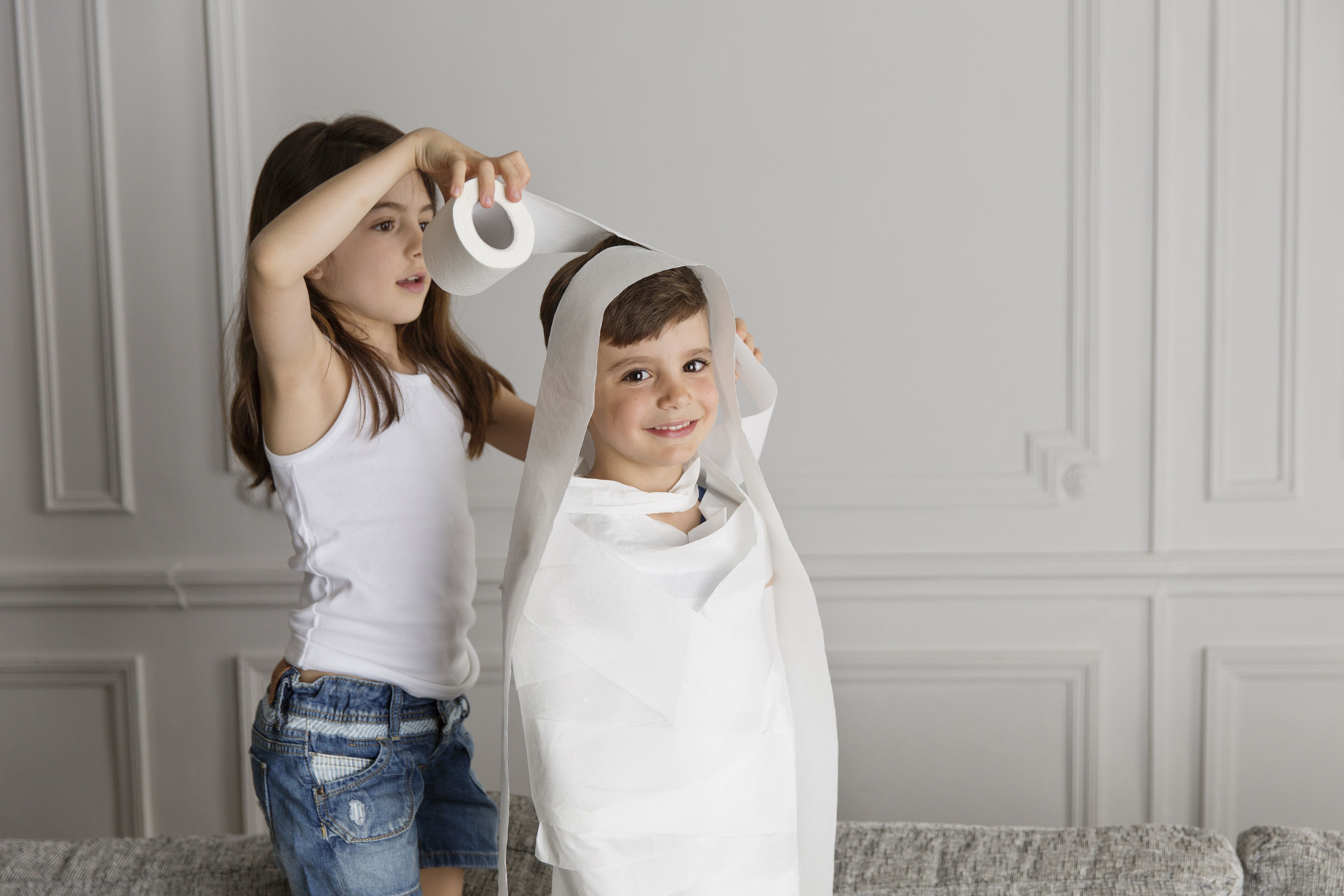 Girl wrapping toilet paper around younger kid