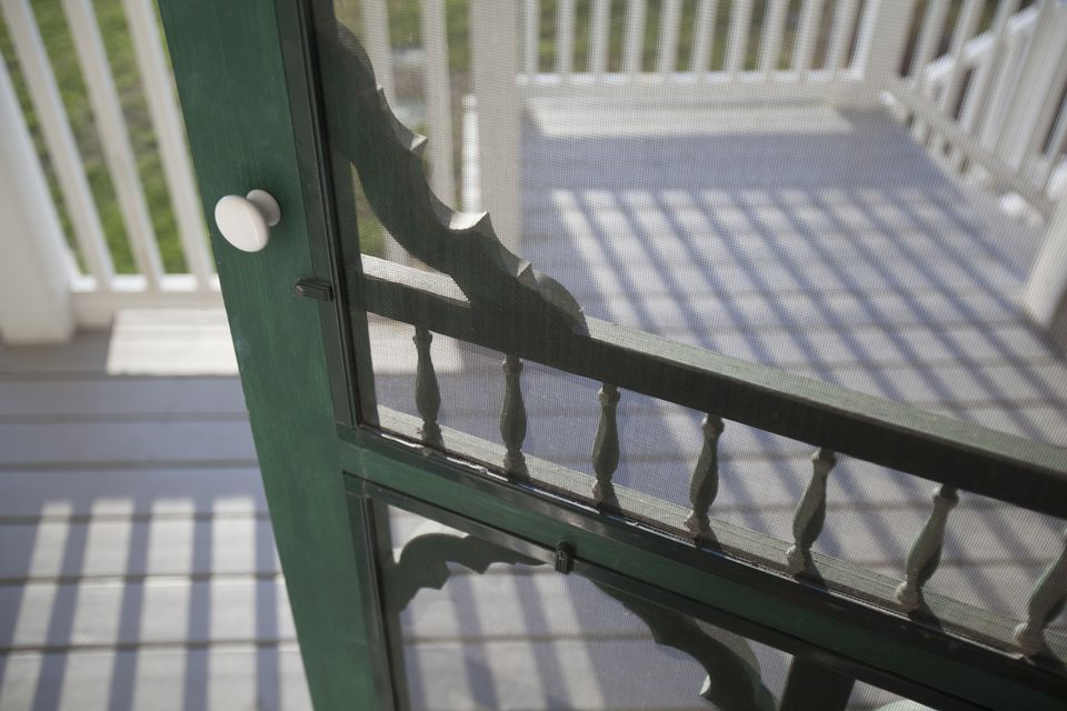 A close up shot of a screen door swinging open onto a sunny porch