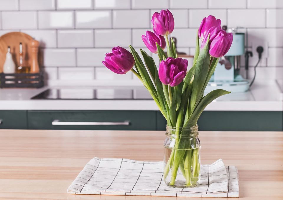 tulips in a vase on the counter