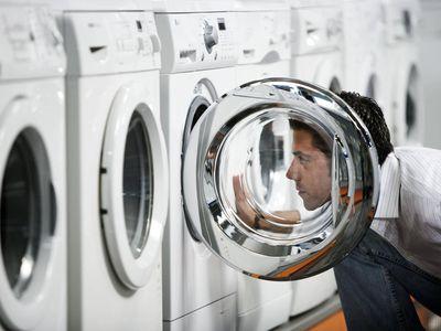 Man inspecting washing machine at the store