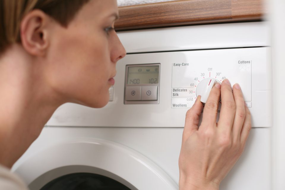 Woman adjusting washing machine