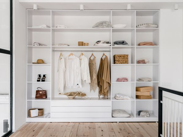 A modern white open closet with lots of shelves.