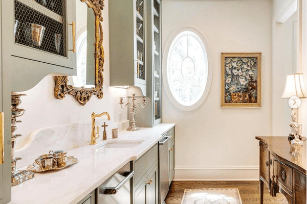 A classic butler's pantry with gold fixtures.