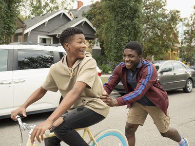Playful teenage boy pushing friend on bicycle on street