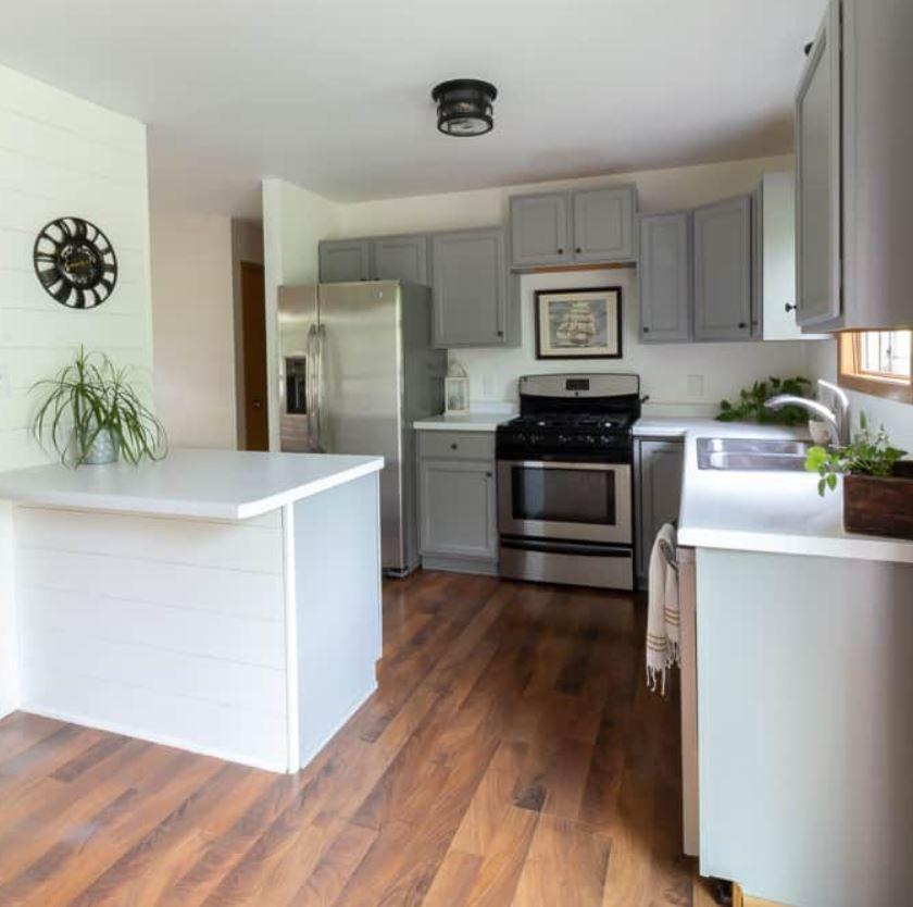 Cocina con gabinetes grises y solapa blanca en la península.