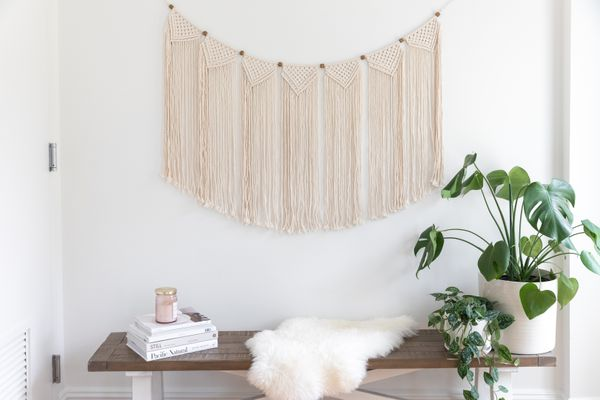 Macrame wall hanging over wooden bench with books stacked and houseplants in white pots
