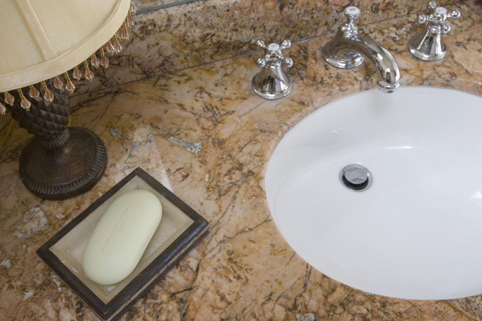 A granite bathroom counter and ceramic sink with a chrome faucet