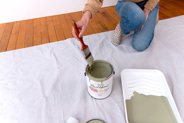 Woman dipping paintbrush into paint can