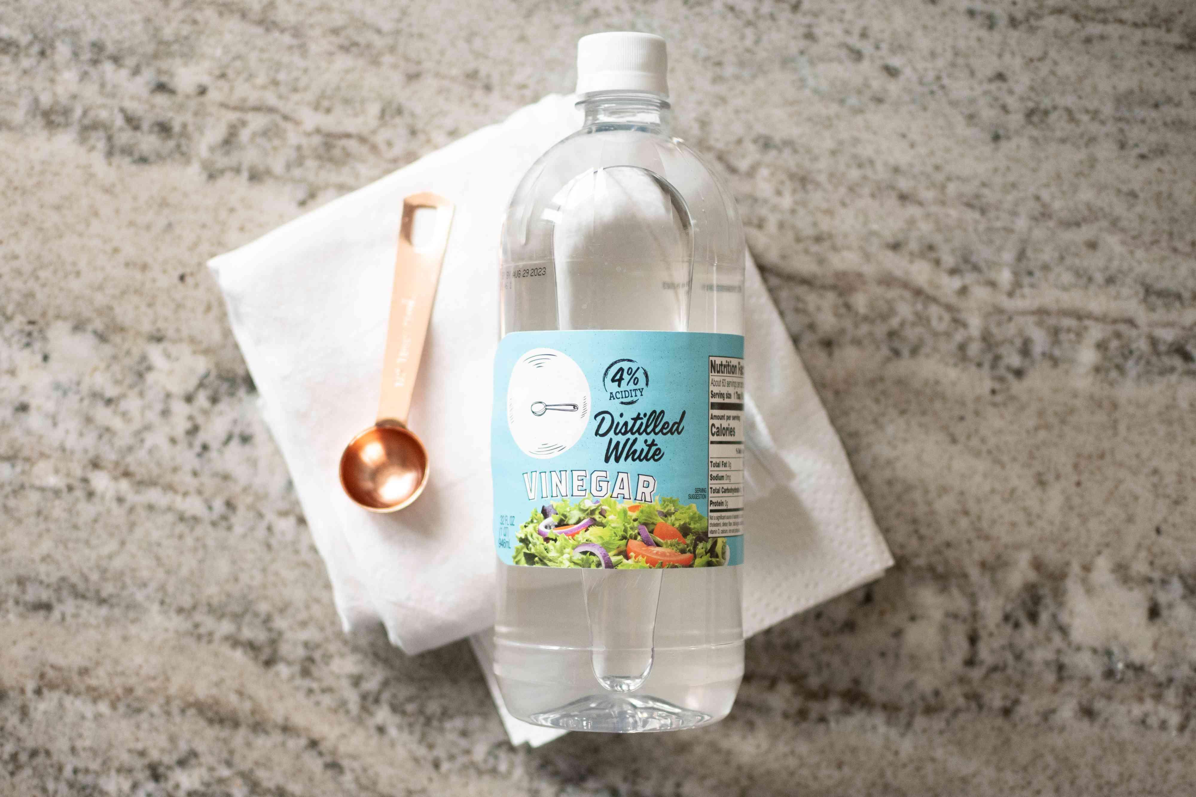 Distilled white vinegar bottle folded paper towels and measuring spoon