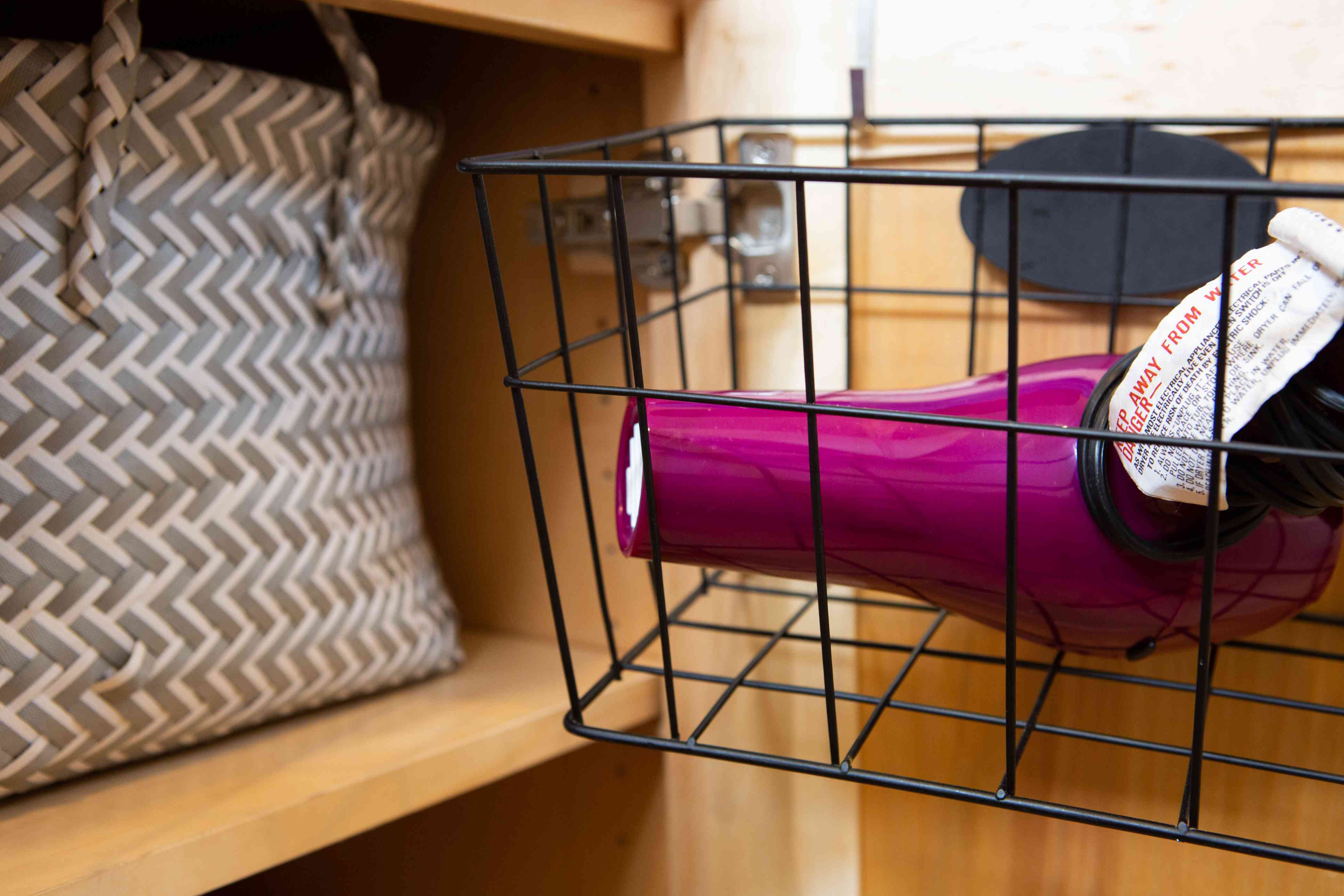 inner cabinet basket holding a hair dryer