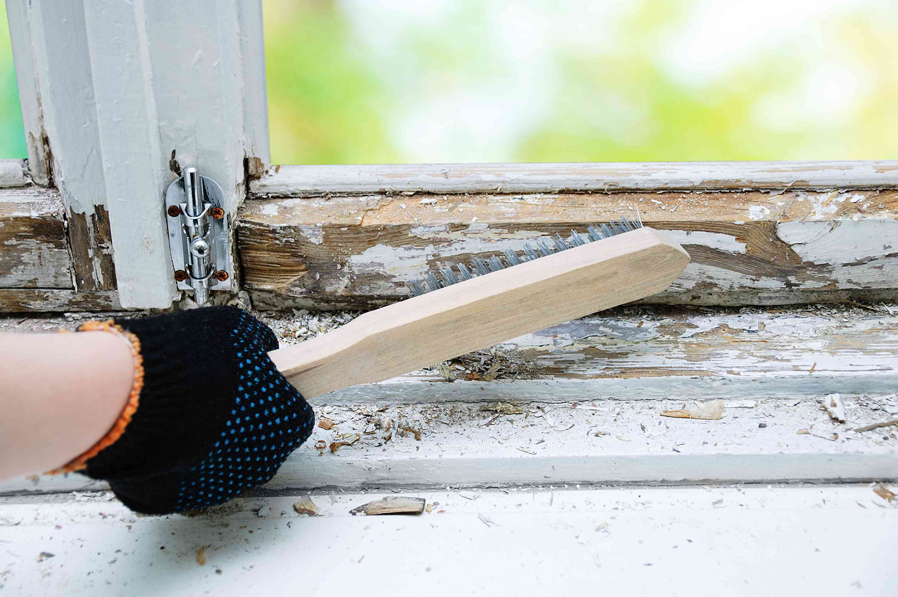 Brush with metal bristles in hand to remove old paint from the window.