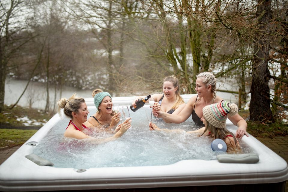 Group of women drinking champagne in hot tub
